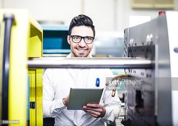 Junger Ingenieur holding digital tablet in der Fabrik