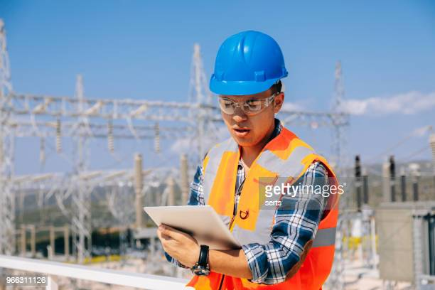 Young engineer man looking and checking electric power station