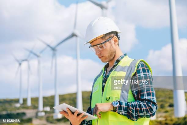 hombre joven ingeniero mirando y comprobando las turbinas de viento en el campo - windmills fotografías e imágenes de stock