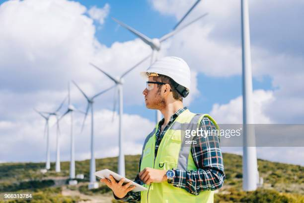 young engineer man looking and checking wind turbines at field - turbine stock photos and pictures