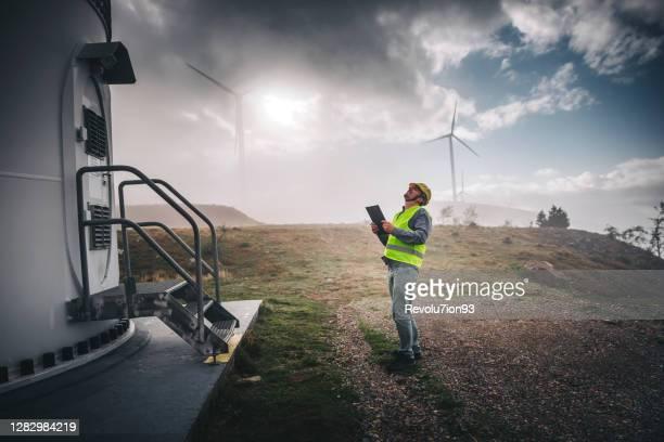 jeune homme d'ingénieur regardant et vérifiant des éoliennes - finance et économie photos et images de collection