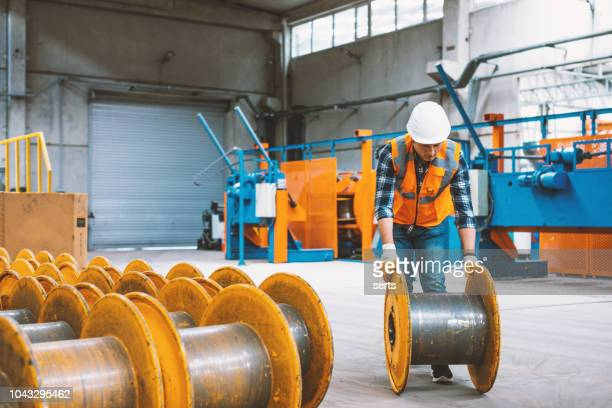 young engineer man working with steel empty cable bobin in factory - drum container stock photos and pictures