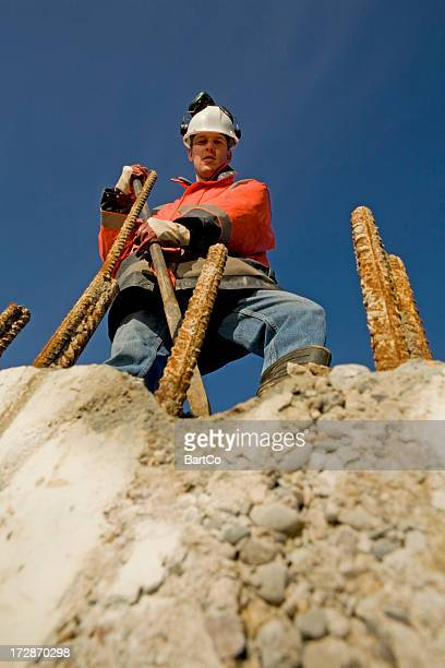 Young engineer on construction site controlling the foundation