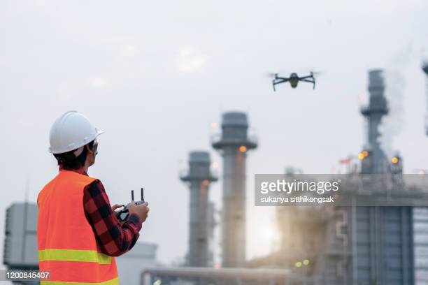 young engineer piloting drone at power plant . video surveillance or industrial inspection. - drone foto e immagini stock