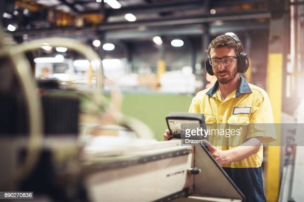 Young engineer setting up the production line machinery in Australian manufacturing company