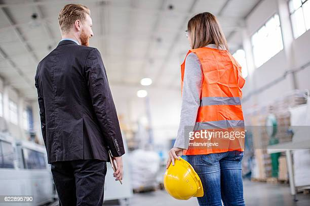 Young engineer with her boss in a factory