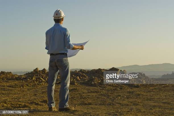 Young engineer with plan on construction site, rear view