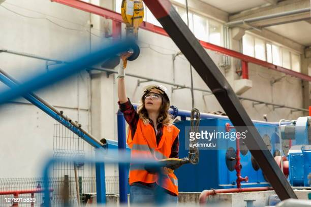 young engineer woman testing using overhead crane controller in factory - health and safety stock pictures, royalty-free photos & images