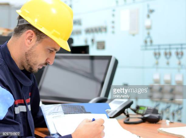 Young engineer working in electrical room in power substation