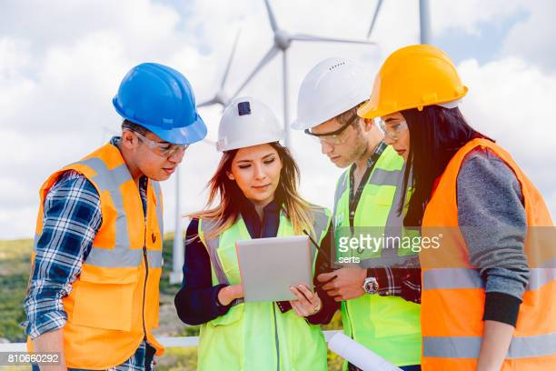 Young engineers and workers having a meeting at wind farm