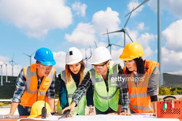 Jonge ingenieurs en werknemers met een bijeenkomst in windpark