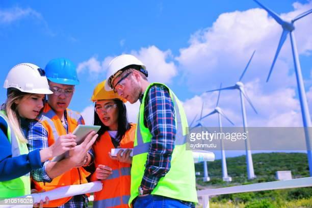 jonge ingenieurs die werkzaam zijn in windpark - alleen volwassenen stockfoto's en -beelden