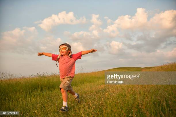 Young English Boy Imagines Flying on Hill
