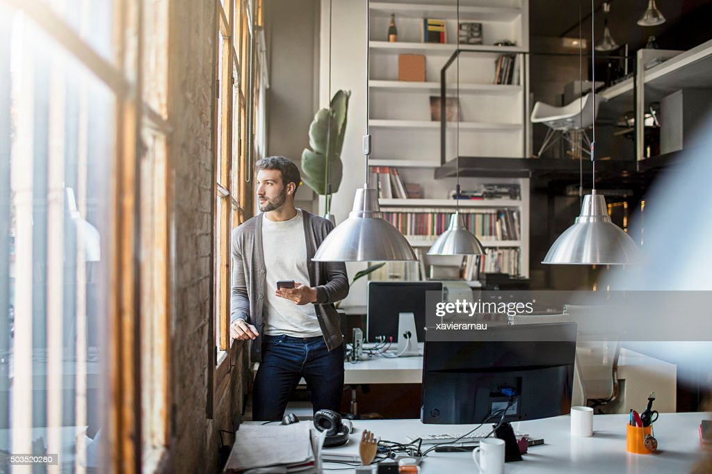 Young entrepreneur looking through the window in the office : Stock Photo