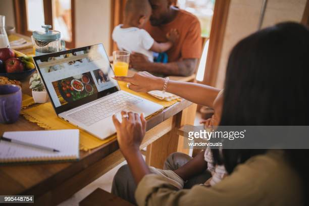 Young entrepreneur mother with children blogging online at home
