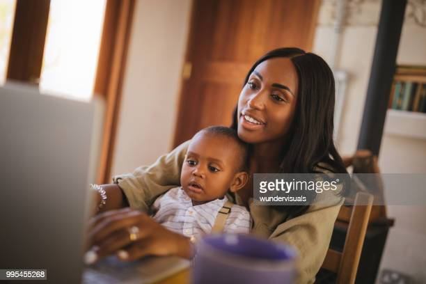Young entrepreneur mother with little child working online from home