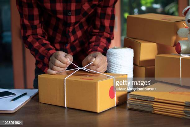 Young entrepreneur packing parcel box and work at home. New generation life style concept.