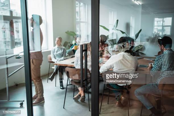 若い起業家は、会議で同僚に新しいビジネス戦略を提示します。 - デザインスタジオ ストックフォトと画像