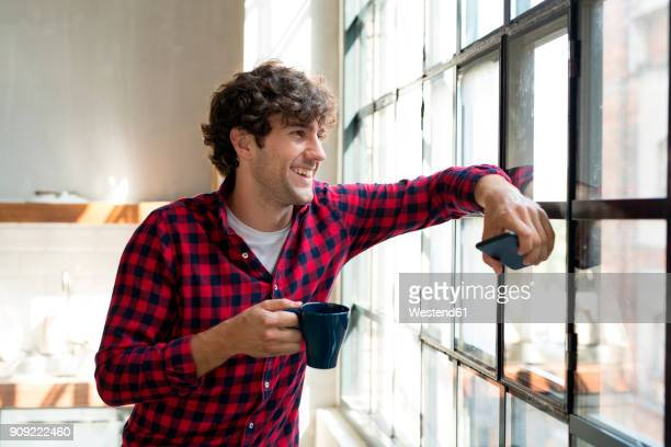 Young entrepreneur standing in company kitchen, drinking coffee