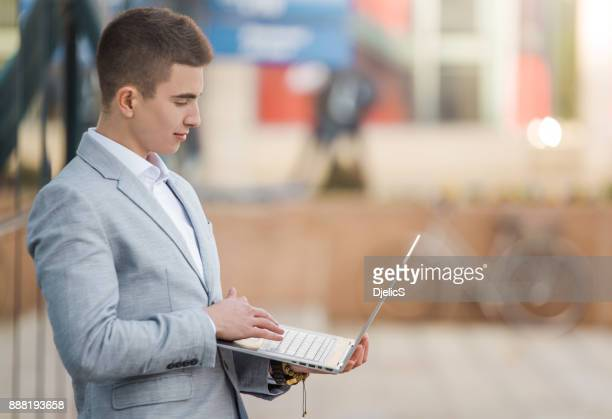Young entrepreneur using his laptop outdoors.