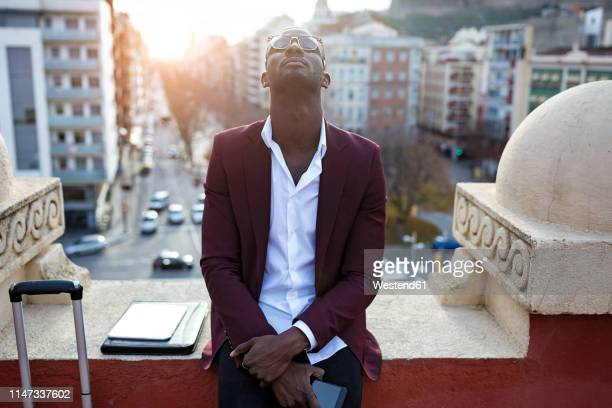 young entrepreneur wating on hotel terrace for his appointment, holding smartphone - escapism stock pictures, royalty-free photos & images