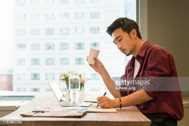 young entrepreneur working in modern cafe - trabalho de freelancer - fotografias e filmes do acervo