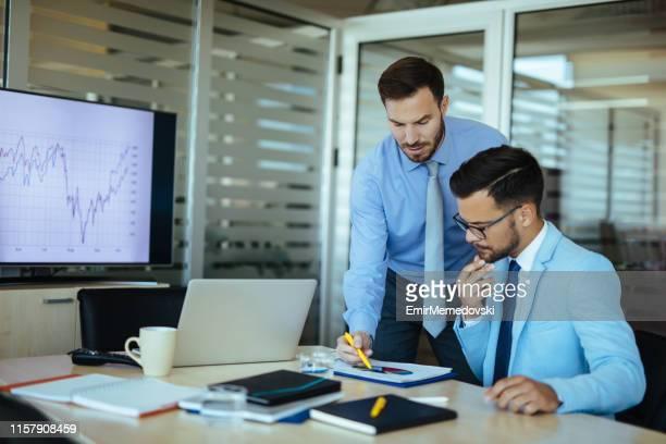 jungunternehmer analysieren business chart im büro - rechnungswesen stock-fotos und bilder