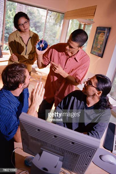 young entrepreneurs huddled around computer - thinkstock stock photos and pictures
