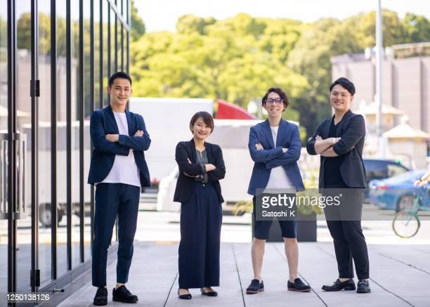 都市に立つ若い起業家、腕が交差 - 4人 ストックフォトと画像
