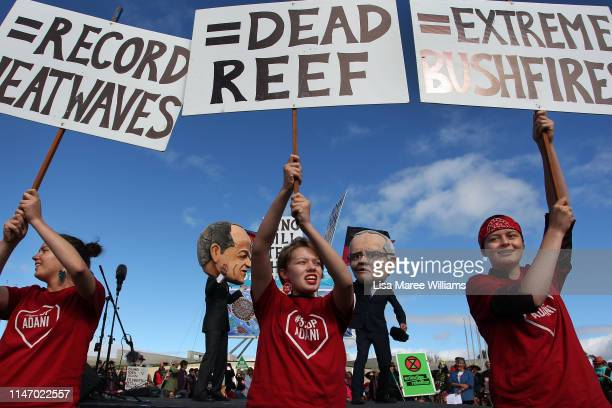 Young environment activists hold protest signs up in front of comedians dressed as Labor leader Bill Shorten and Prime Minister Scott Morrison on May...