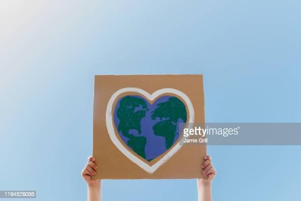 young environmental activist holding sign against blue sky - activista fotografías e imágenes de stock