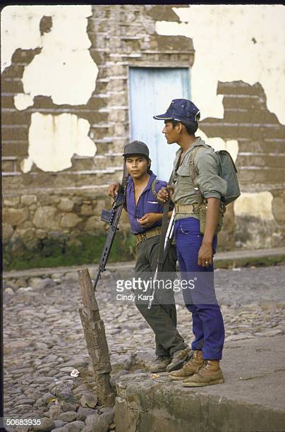 Young ERP guerrillas armed with rifles standing around in town