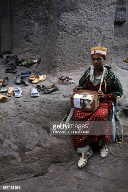 A young Ethiopian altar boy dressed in colorful traditional costume is collecting alms just outside one of the underground churches in Lalibela...