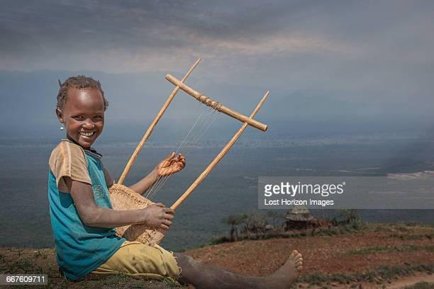 Young Ethiopian girl playing a self made instrument, Lalibela, Ethiopia