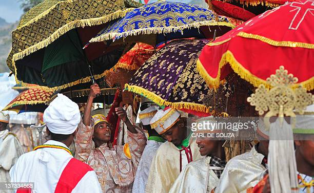 A young Ethiopian Orthodox Christian adjusts his umbrella during the annual festival of Timkat in Lalibela Ethiopia which celebrates the Baptism of...