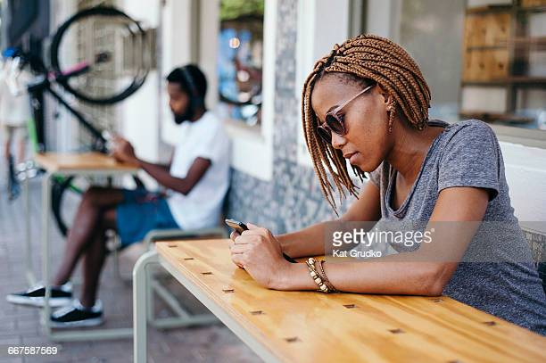 Young ethnic African couple listening to and reading mobile devices outside shop in trendy suburb in Braamfontein Johannesburg South Africa