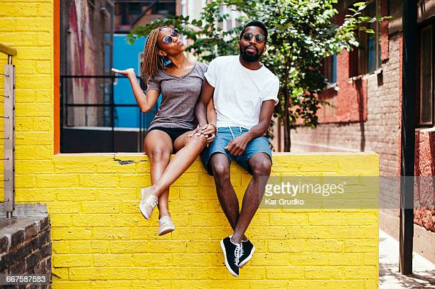 Young ethnic African couple sitting on wall in trendy suburb in Braamfontein Johannesburg South Africa