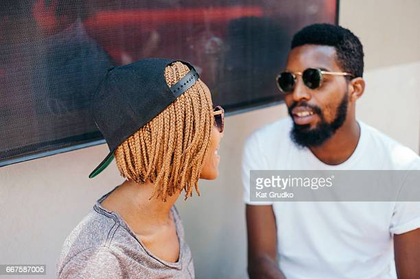 Young ethnic African couple sitting outside shop in trendy suburb in Braamfontein Johannesburg South Africa