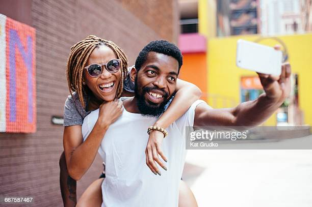 young ethnic african couple taking a selfie with a mobile device outside shops in trendy suburb in braamfontein johannesburg south africa - black alley stock photos and pictures