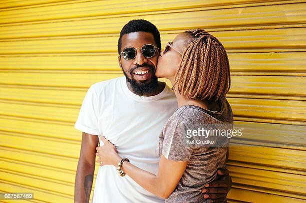 young ethnic african woman kissing man on cheek standing in front of yellow metal door in trendy suburb in braamfontein johannesburg south africa - personas sin dientes fotografías e imágenes de stock