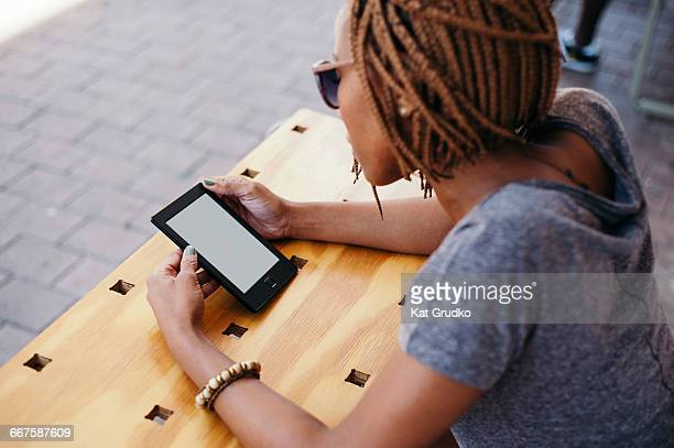 Young ethnic African woman reading mobile device outside shop in trendy suburb in Braamfontein Johannesburg South Africa