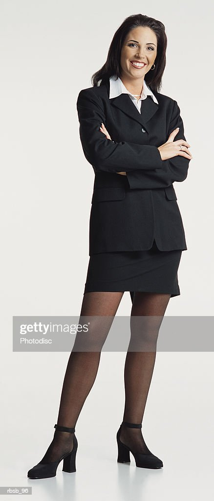 young ethnic businesswoman with long dark hair wears a dark business suit faces camera arms crossed : Foto de stock