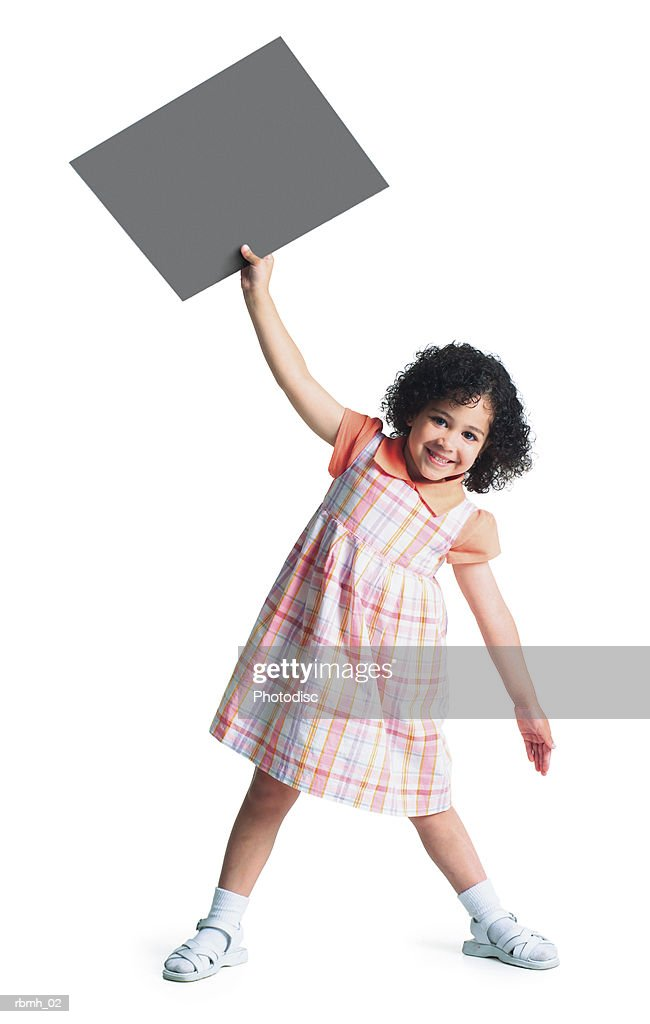 young ethnic girl in pastel dress holds blank sign in air with one hand tilts to other side smiling : Stockfoto