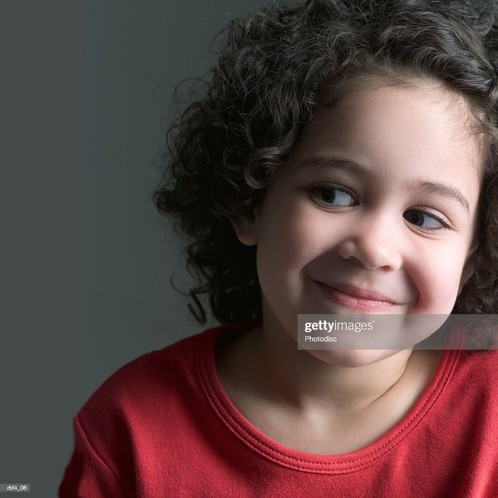 A young ethnic girl wearing a red shirt tilts her head to the side smiles slightly while glancing to the left : Stockfoto