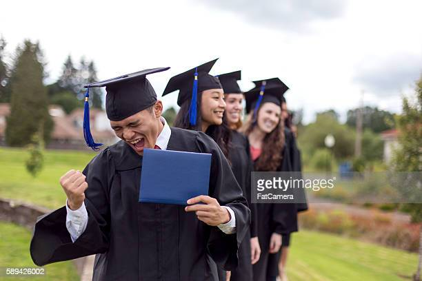 young ethnic male celebrates after receiving his diploma - diploma stock photos and pictures