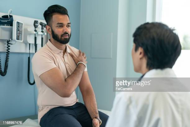 young ethnic man in consultation with doctor - shoulder stock pictures, royalty-free photos & images