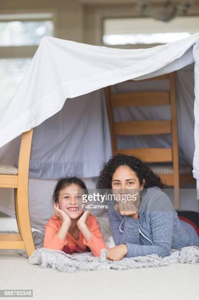 Junge ethnischen Mama und Tochter Handauflegen Wohnzimmerboden und reden über das Leben