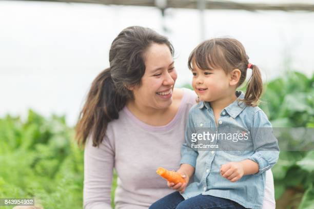 Young ethnic mom holds her daughter on lap who is snacking on a carrot from the garden