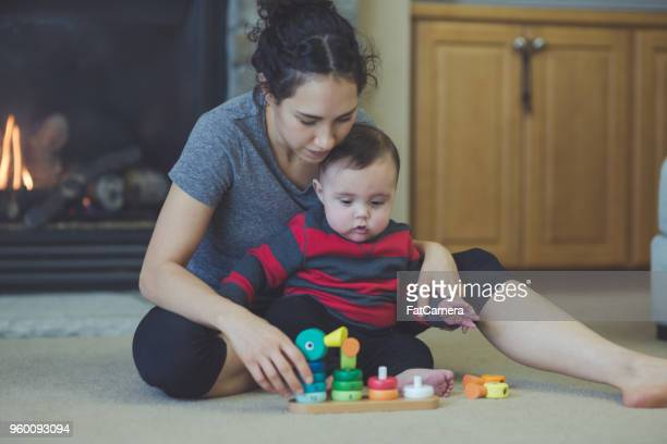 Young ethnic mom playing with her infant son in the living room