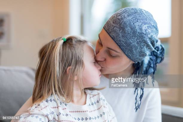 young ethnic mom with cancer holds her daughter - cancer stock photos and pictures